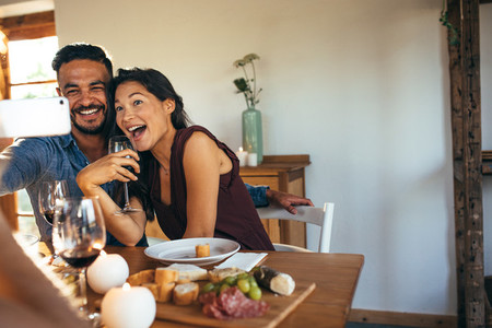 Couple taking selfie at dinner party indoors