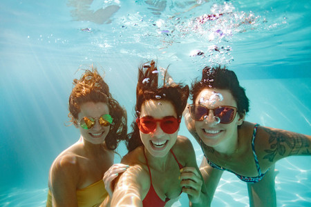 Cheerful friends making selfie underwater in pool