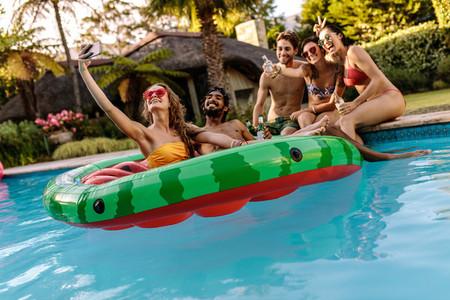 Joyful friends with drinks taking selfie by the pool