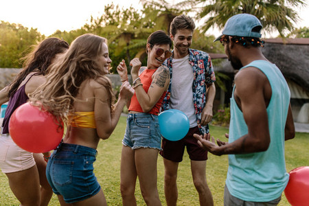 Group of friends playing balloon bursting game at party
