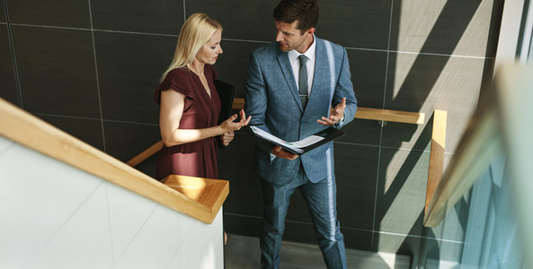 Businessman talking with female colleague in office stairway