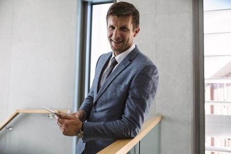 Businessman in office corridor with digital tablet