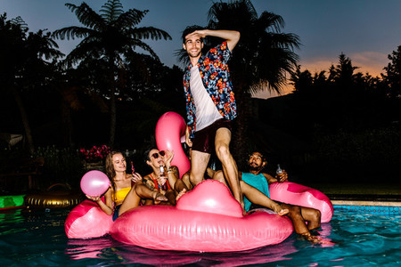 Group of men and women partying in the pool