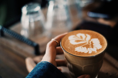 Hand holding hot coffee cup