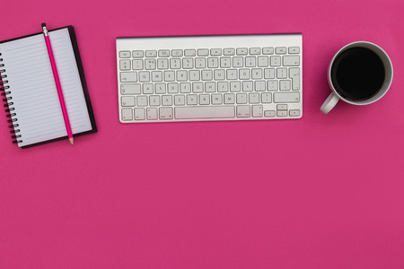 Minimal computer keyboard notebook on bright pink background