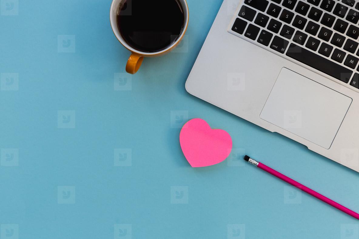 Minimal laptop computer love pink heart on bright blue backgroun