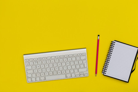Minimal computer keyboard notebook on bright yellow background