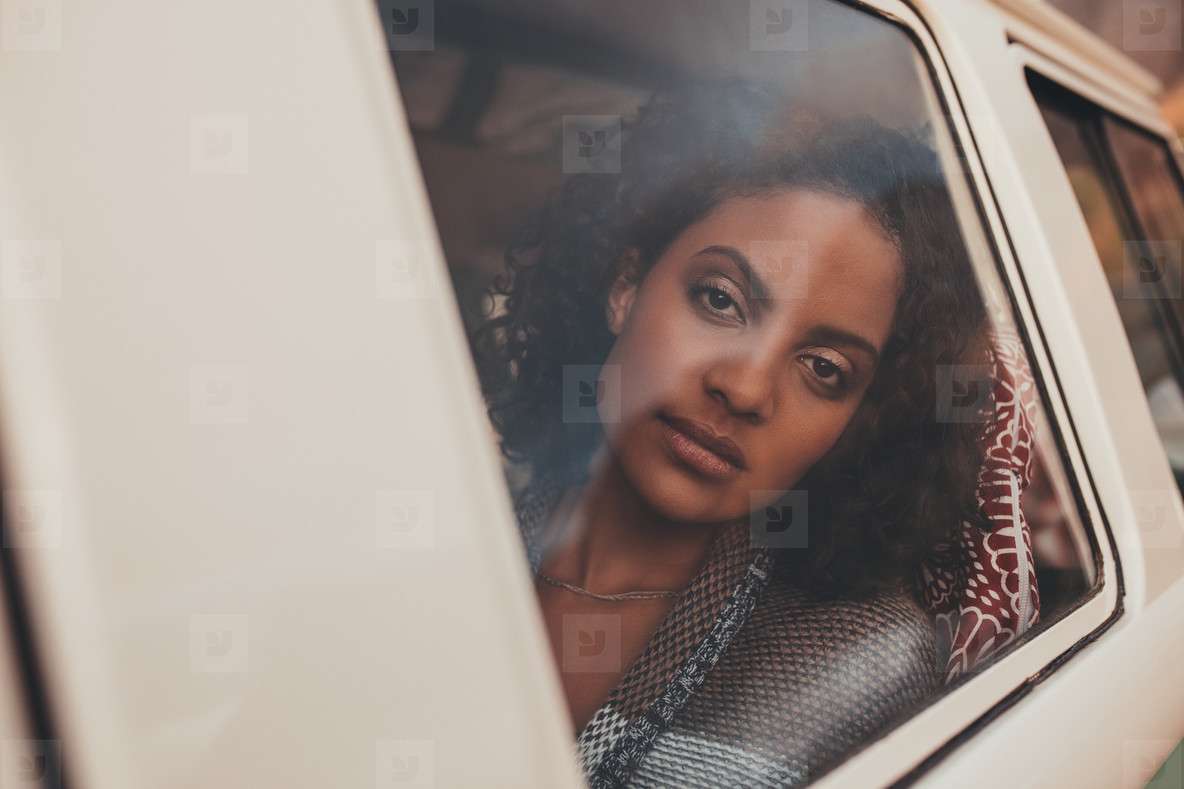 Thoughtful woman travelling by a van