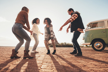 Friends dancing outdoors on road