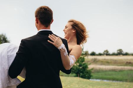 Bridegroom carrying bride on wedding day
