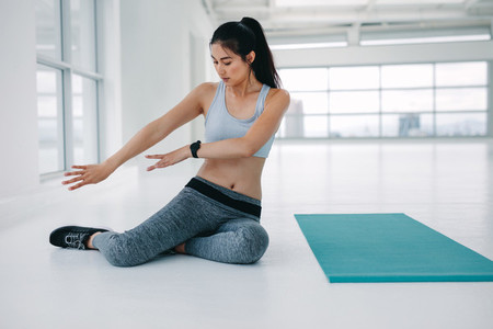 Woman rehearsing yoga poses at fitness studio