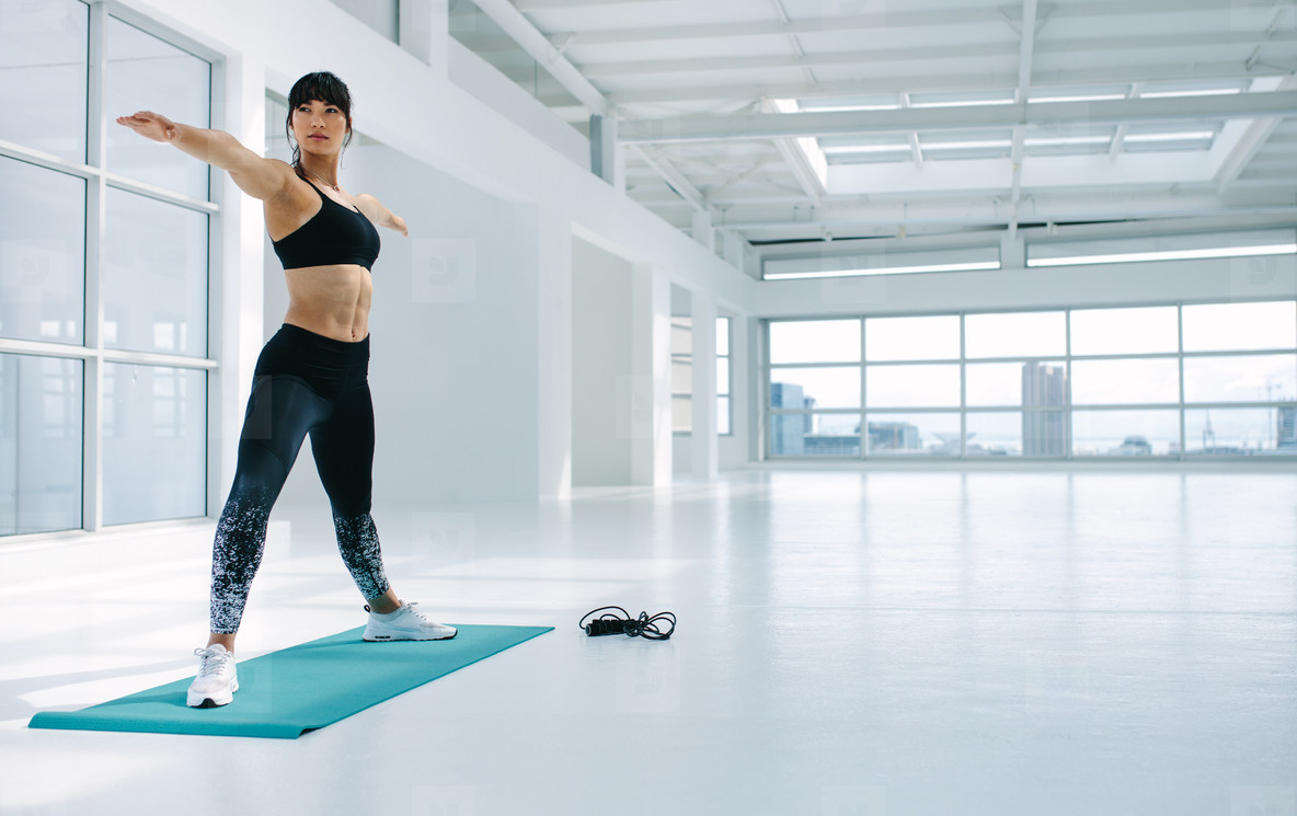 Fit woman exercising yoga in fitness studio