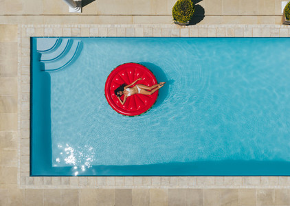 Woman relaxing on floating mattress in pool
