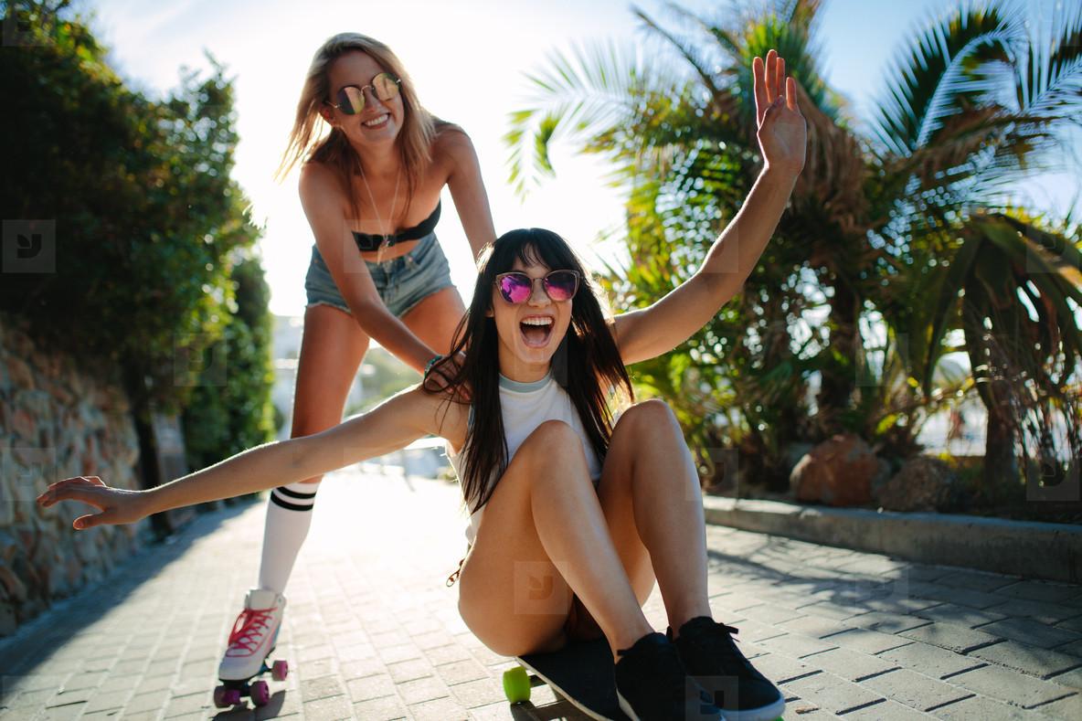Girl pushing friend on the skateboard