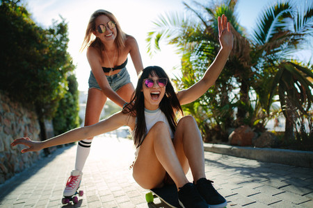 Girl pushing friend on the skateboard