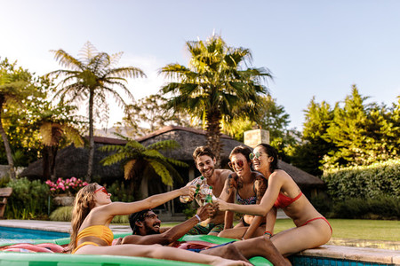Friends enjoying and toasting beers at pool party