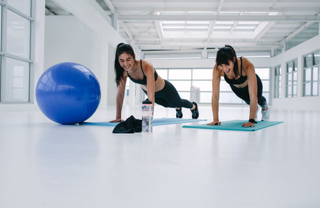 Two female exercising in fitness studio