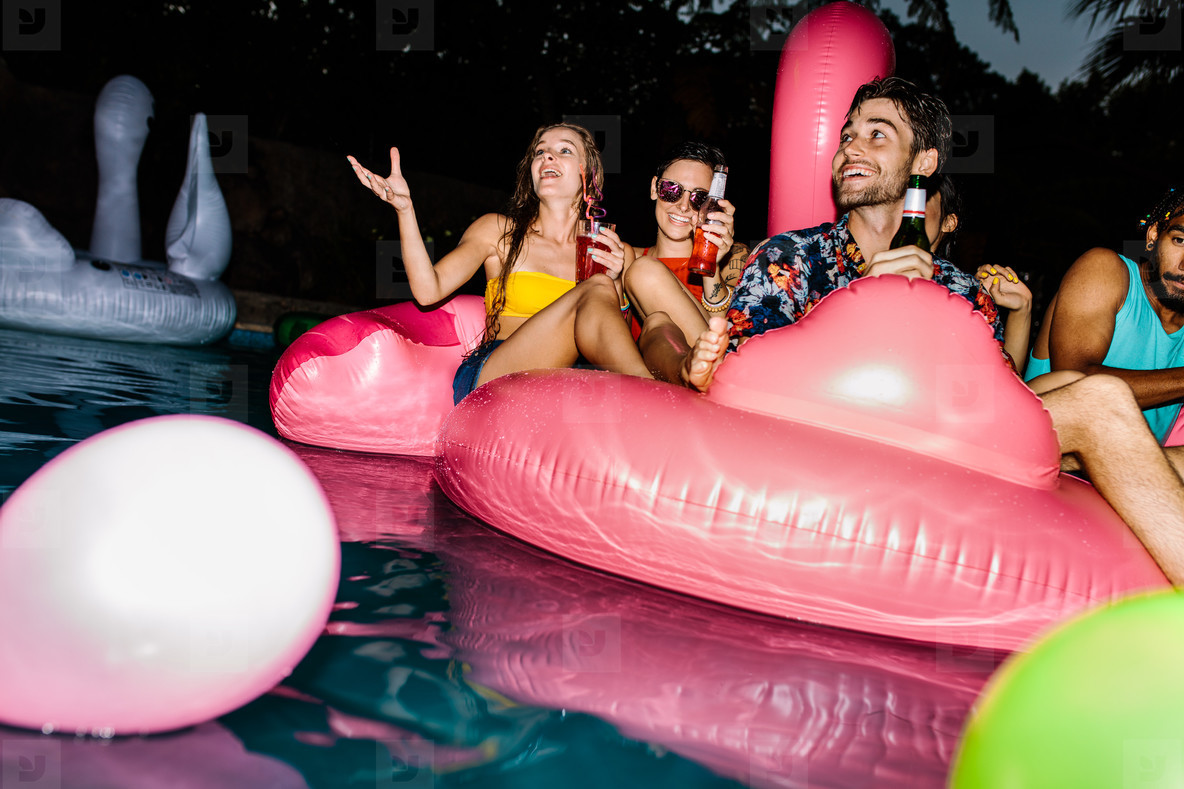 Friends enjoying pool party in evening