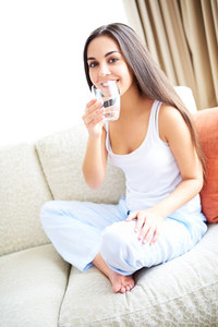 Woman smiling holding glass of water near mouth