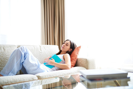 Woman asleep on couch with book