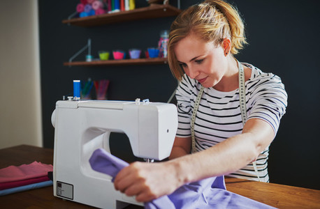 Young fashion designer using a sewing machine