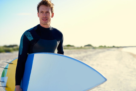 Serious handsome male surfer posing with his board