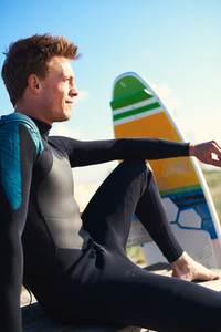 Profile of a young surfer relaxing at the beach