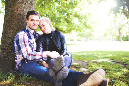 Romantic Couple at the Park Sitting Beside a Tree