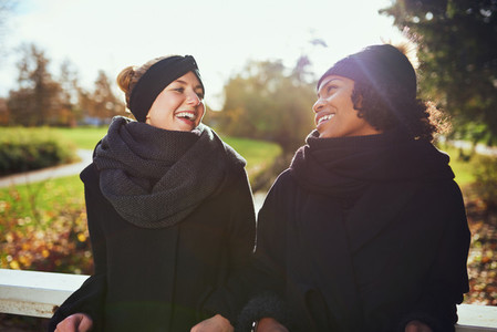 Two women in warm clothes standing on bridge in park