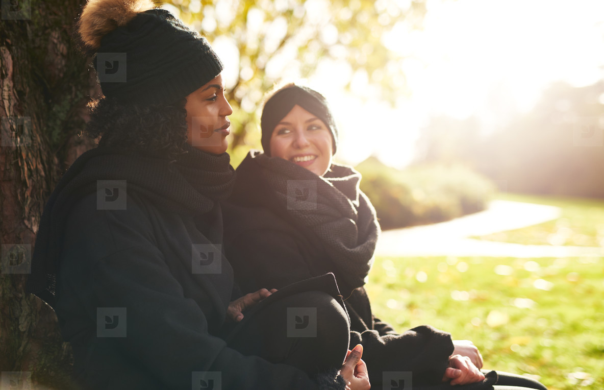 Two young women sitting in park and smiling