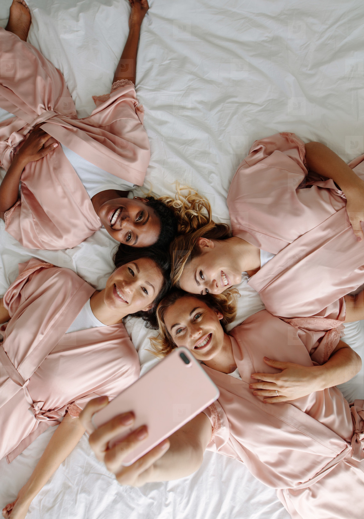 Bride taking selfie with bridesmaids while lying on bed