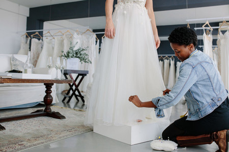 Female designer making adjustment to bridal gown