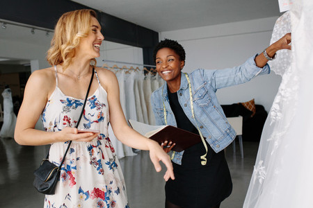 Shop assistant helps the bride in choosing bridal dress