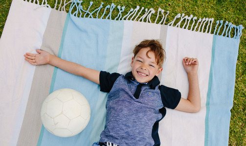 Boy with football enjoying in a park
