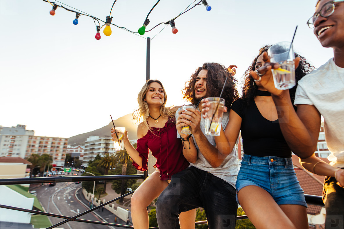 Young people partying on terrace with drinks