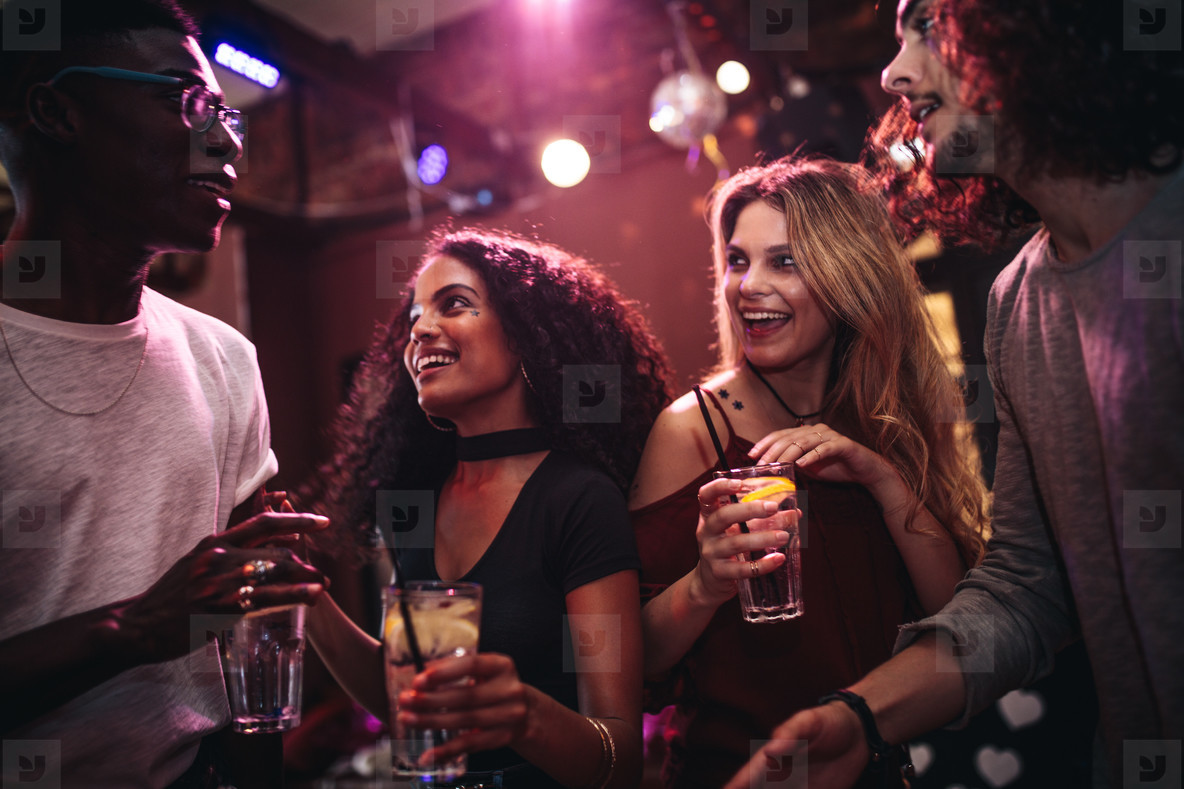 Happy friends enjoying nightout at bar