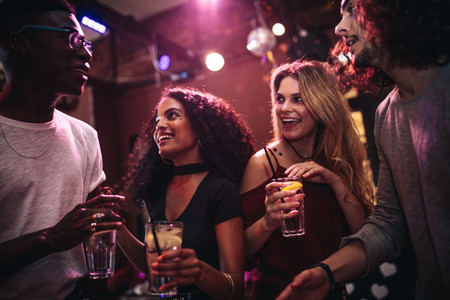 Happy friends enjoying nightout at bar