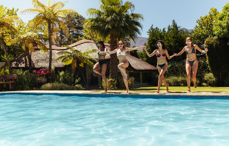 Women friends jumping in the swimming pool