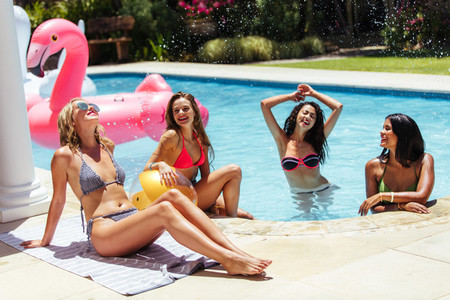 Group of women having fun at the resort poolside