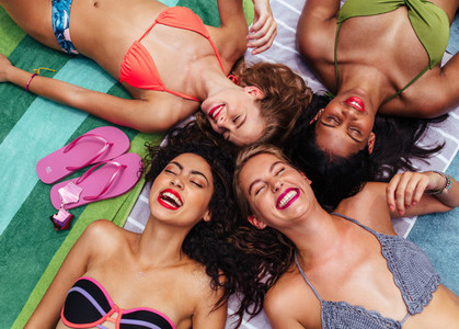 Group of female friends enjoying by poolside