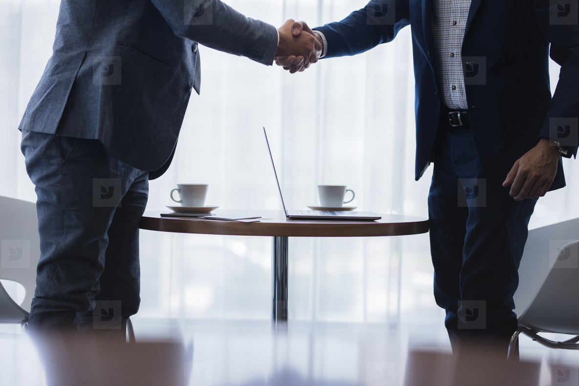 Businessmen shaking hands after successful meeting