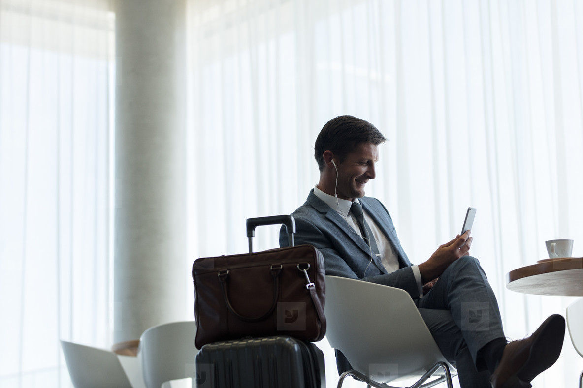 Businessman sitting at airport lounge with mobile phone
