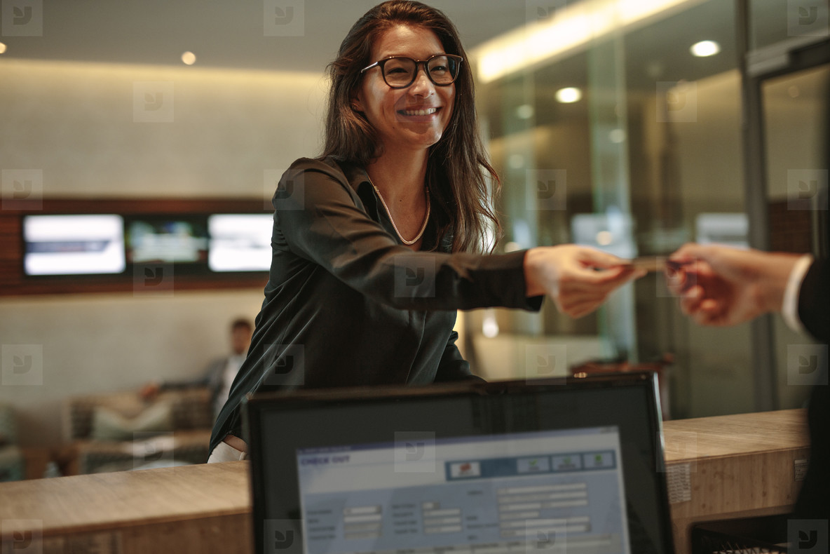 Business woman receiving key card for hotel room