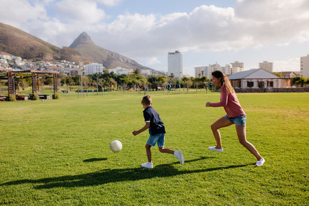 Mother and son playing football in park