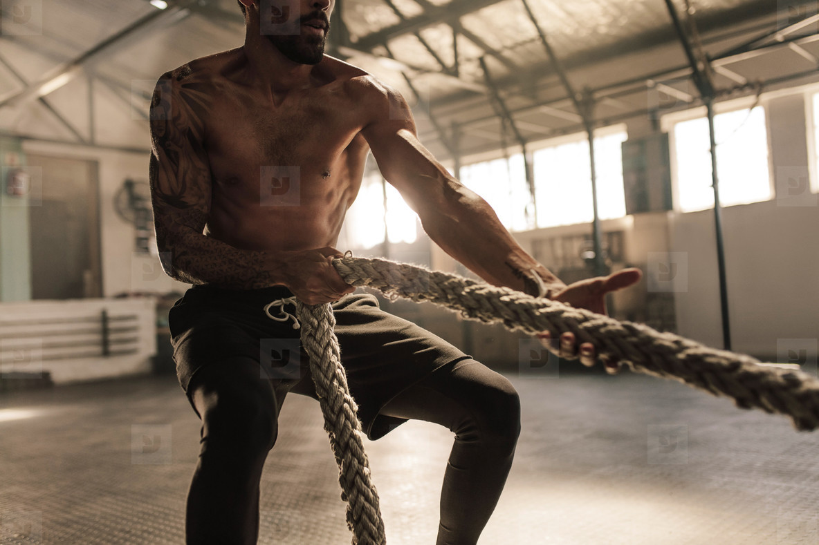 Athlete doing exercises with rope at gym