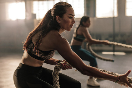 Fitness females pulling rope at gym