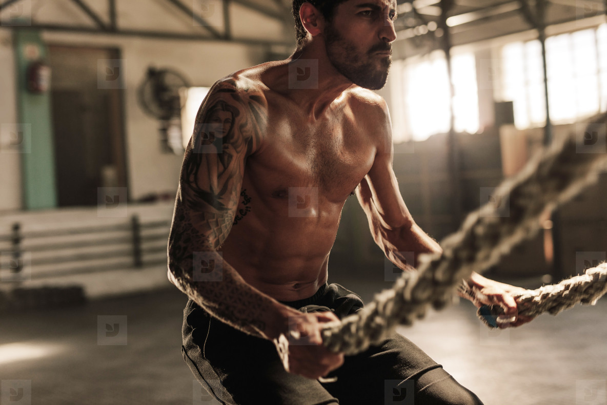 Powerful man exercising with battle ropes at gym