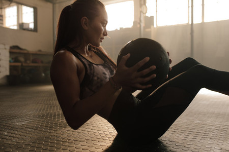 Determined woman exercising with medicine ball in gym
