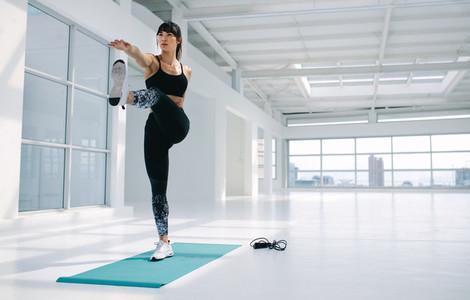 Woman practising yoga asana in fitness studio