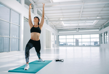 Beautiful woman doing Virabhadrasana yoga in gym